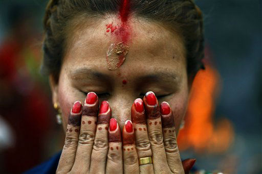 A Nepalese Hindu woman offers prayers at the Pashupatinath temple during Teej festival celebrations in Katmandu, Nepal, Tuesday, Sept. 18, 2012. During the festival, Nepalese Hindu women observe a day-long fast and pray for their husbands and for a happy married life. Those who are unmarried pray for a good husband. &#40;AP Photo&#47;Niranjan Shrestha&#41; <span class=meta>(AP Photo&#47; Niranjan Shrestha)</span>