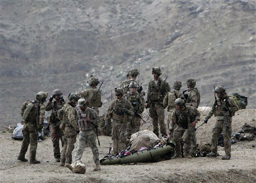 U.S. soldiers evacuate a dead body as they arrive to the scene after a NATO helicopter crashed in a field killing two American service members, near Gerakhel, eastern Afghanistan, Tuesday, April 9, 2013. The U.S.-led International Security Assistance Force said the cause of the crash is under investigation but initial reporting indicates there was no enemy activity in the area at the time. It did not immediately identify the nationalities of those killed. But a senior U.S. official confirmed they were Americans. &#40;AP Photo&#47;Rahmat Gul&#41; <span class=meta>(AP Photo&#47; Rahmat Gul)</span>