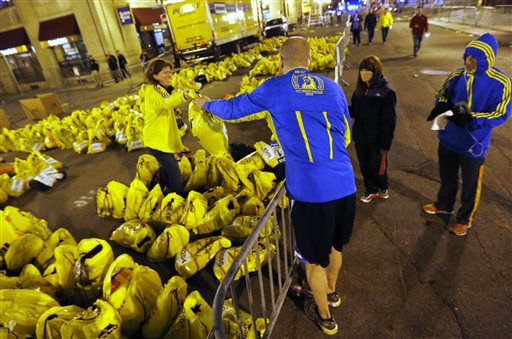 A runner retrieves his belongings from a Boston Athletics Association worker at a sorting area near the site of an explosion at the finish line of the Boston Marathon in Boston, Monday, April 15, 2013. (AP Photo/Michael Dwyer)