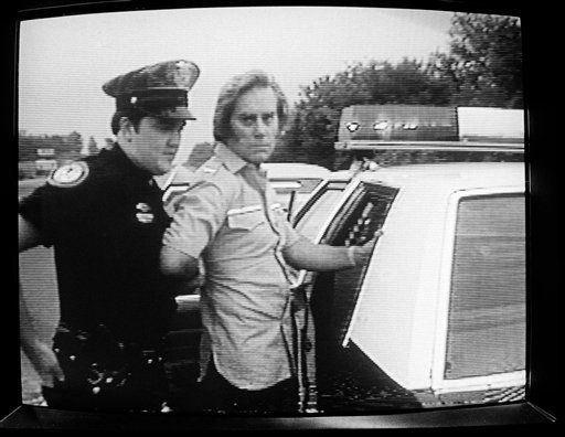 Country music star George Jones is put in a patrol car by Brentwood, Tenn., police officer Tommy Campsey after Jones was picked up for drunk driving on Interstate 65 about 5 miles north of Franklin, Tenn., May 26, 1982.  Jones spent approximately four hours in the Williamson County jail before being released on &#36;500 bond.  &#40;AP Photo&#47;WSMV-TV&#47;David Goins&#41; <span class=meta>(AP Photo&#47; David Goins)</span>