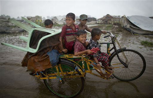 "<div class=""meta ""><span class=""caption-text "">Internally displaced Rohingya man pushes a rickshaw with children and belongings leaving a camp for displaced Rohingya people in Sittwe, northwestern Rakhine State, Myanmar, Thursday, May 16, 2013. Members of the displaced Rohingya minority started to evacuate for safer shelters ahead of the arrival of Cyclone Mahasen. (AP Photo/Gemunu Amarasinghe) (AP Photo/ Gemunu Amarasinghe)</span></div>"
