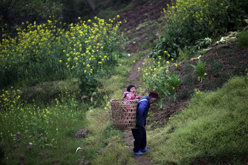 An elderly Chinese  woman caries a baby piggyback in a traditional basket on the outskirts of Chongqing, China, Tuesday March 19, 2013. &#40;AP Photo&#47;Eugene Hoshiko&#41; <span class=meta>(AP Photo&#47; Eugene Hoshiko)</span>
