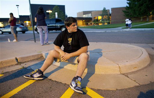 Eyewitness Chandler Brannon, 25, sits outside Gateway High School where witnesses were brought for questioning after a shooting at a movie theater showing the Batman movie &#34;The Dark Knight Rises,&#34; Friday, July 20, 2012 in Aurora.  A gunman wearing a gas mask set off an unknown gas and fired into the crowded movie theater killing 12 people and injuring at least 50 others, authorities said. &#40;AP Photo&#47;Barry Gutierrez&#41; <span class=meta>(AP Photo&#47; Barry Gutierrez)</span>