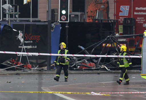 Firefighters walk pass the section of damaged crane on the ground after a helicopter crashed into the crane on top of a building in central London, Wednesday Jan. 16, 2013. Police say two people were killed when a helicopter crashed Wednesday during rush hour in central London after apparently hitting a construction crane on top of a building. &#40;AP Photo&#47;Sang Tan&#41; <span class=meta>(AP Photo&#47; Sang Tan)</span>