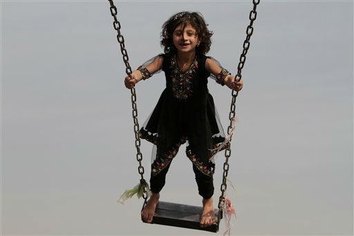 An Afghan girl enjoys a swing in an amusement park in Jalalabad, Afghanistan, Monday, Nov 12, 2012. &#40;AP Photo&#47;Rahmat Gul&#41; <span class=meta>(AP Photo&#47; Rahmat Gul)</span>