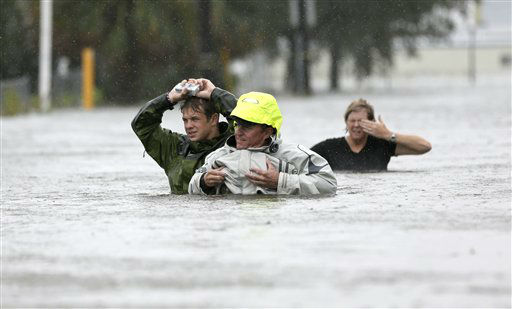 Chuck Cropp, center, his son Piers, left, and wife Liz, right, wade through floodwaters from Hurricane Isaac Wednesday, Aug. 29, 2012, in New Orleans. As Isaac made landfall, it was expected to dump as much as 20 inches of rain in several parts of Louisiana. &#40;AP Photo&#47;David J. Phillip&#41; <span class=meta>(AP Photo&#47; David J. Phillip)</span>