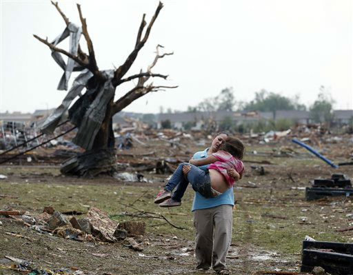 A woman carries a child through a field near the collapsed Plaza Towers Elementary School in Moore, Okla., Monday, May 20, 2013.  A tornado as much as a mile wide with winds up to 200 mph roared through the Oklahoma City suburbs Monday, flattening entire neighborhoods, setting buildings on fire and landing a direct blow on an elementary school. &#40;AP Photo Sue Ogrocki&#41; <span class=meta>(AP Photo&#47; Sue Ogrocki)</span>