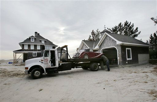 Adrian Agullar removes a ruined vintage automobile from the garage of a storm-damaged beach front home in Mantoloking, N.J., Friday, Feb. 22, 2013. New Jersey has reached another milestone in its recovery 116 days after Superstorm Sandy struck. One of the hardest-hit Jersey shore communities, Mantoloking, will allow its residents to begin moving back home Friday. It is the last shore town to do so. &#40;AP Photo&#47;Mel Evans&#41; <span class=meta>(AP Photo&#47; Mel Evans)</span>
