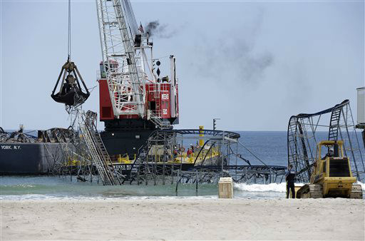 "<div class=""meta ""><span class=""caption-text "">A huge crane works in Seaside Heights, N.J., Tuesday, May 14, 2013, to dismantle the Jet Star Roller Coaster which has been sitting in the ocean after part of the Casino Pier was destroyed during Superstorm Sandy. (AP Photo/Mel Evans) (AP Photo/ Mel Evans)</span></div>"