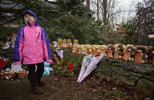 Ava Staiti, 7, of New Milford, Conn., looks up at her mother Emily Staiti, not pictured, while visiting a sidewalk memorial with 26 teddy bears, each representing a victim of the Sandy Hook Elementary School shooting, Sunday, Dec. 16, 2012, in Newtown, Conn. A gunman walked into Sandy Hook Elementary School in Newtown Friday and opened fire, killing 26 people, including 20 children. &#40;AP Photo&#47;David Goldman&#41; <span class=meta>(AP Photo&#47; David Goldman)</span>