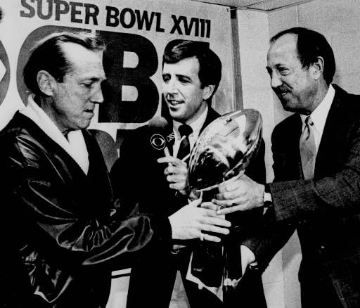 Los Angeles Raiders general managing partner Al Davis, left, receives the Super Bowl trophy from NFL commissioner Pete Rozelle, right, as CBS-TV&#39;s Brent Musburger watches in the locker room at Tampa Stadium in Tampa, Fla., Jan. 23, 1984. &#40;AP Photo&#47;stf&#41; <span class=meta>(AP Photo&#47; XSS RJK ROB)</span>