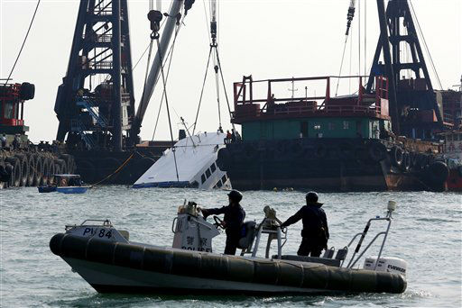 Police officers on a small boat secure the area around a half submerged boat Tuesday Oct. 2, 2012 after Monday night&#39;s collision near Lamma Island, off the southwestern coast of Hong Kong Island. The boat packed with revelers on a long holiday weekend collided with a ferry and sank, killing at least 36 people and injuring dozens, authorities said.  &#40;AP Photo&#47;Vincent Yu&#41; <span class=meta>(AP Photo&#47; Vincent Yu)</span>