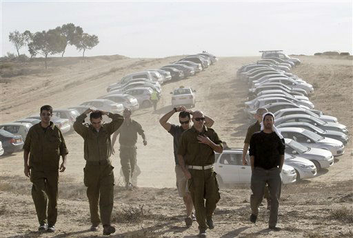 Israeli military reservists arrive at a gathering point in Mishmar Hanegev, southern Israel, Friday, Nov. 16, 2012. The Israeli government approved on Thursday the mobilization of up to 30,000 reservists for a possible ground incursion into Gaza.&#40;AP Photo&#47;Ilan Assayag&#41; <span class=meta>(AP Photo&#47; Ilan Assayag)</span>
