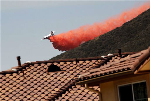 A firefighting aircraft drops fire retardant along a hill side near homes in Thousand Oaks, Calif. on Thursday, May 2, 2013.  A wildfire fanned by gusty Santa Ana winds raged along the fringes of Southern California communities on Thursday, forcing evacuation of homes and a university while setting recreational vehicles ablaze.  &#40;AP Photo&#47;Nick Ut&#41; <span class=meta>(AP Photo&#47; Nick Ut)</span>