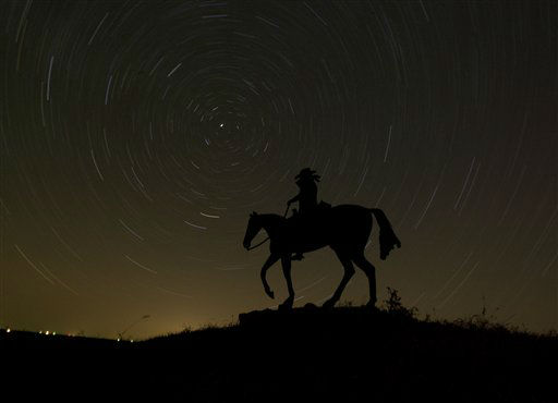 In this photo made using an hour-long time exposure, stars swirl behind a sign for a ranch near Olsburg, Kan. early Tuesday morning, Nov. 13, 2012. (AP Photo/Charlie Riedel)
