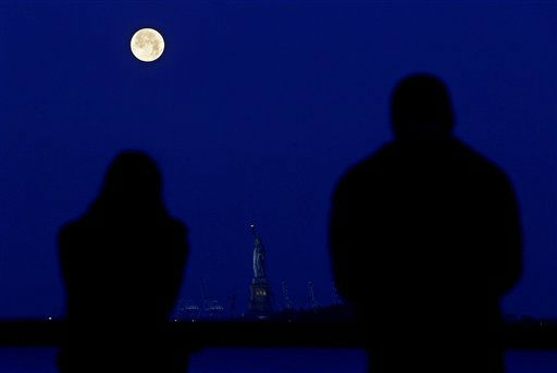 Friends Christina Magnotta, left, and Billy  Becerra, both from White Plains, N.Y., look on as the supermoon glows over the Statue of Liberty, Sunday, June 23, 2013, in New York. The larger than normal moon called the &#34;Supermoon&#34; happens only once this year as the moon on its elliptical orbit is at its closest point to earth and is 13.5 percent larger than usual. &#40;AP Photo&#47;Julio Cortez&#41; <span class=meta>(AP Photo&#47; Julio Cortez)</span>