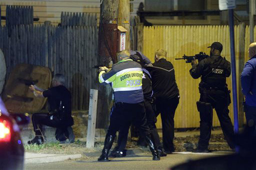 Police officers aim their weapons Friday, April 19, 2013, in Watertown, Mass. A tense night of police activity that left a university officer dead on campus just days after the Boston Marathon bombings and amid a hunt for two suspects caused officers to converge on a neighborhood outside Boston, where residents heard gunfire and explosions.&#40;AP Photo&#47;Matt Rourke&#41; <span class=meta>(AP Photo&#47; Matt Rourke)</span>