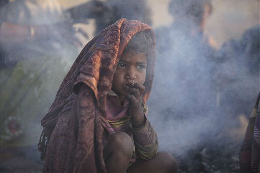 "<div class=""meta ""><span class=""caption-text "">A homeless child sits by a bonfire on a wayside in the morning in Jammu, India, Thursday, Nov. 8, 2012. (AP Photo/Channi Anand) (AP Photo/ Channi Anand)</span></div>"