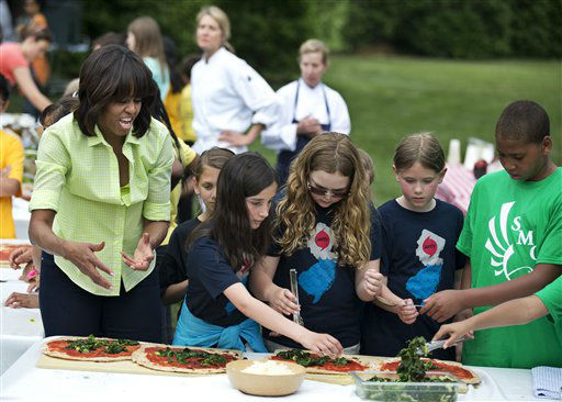 First lady Michelle Obama, left, gives instructions to students from Long Beach Island Grade School in Ship Bottom, N.J., navy blue shirts and Sarah Moore Greene Magnet Technology Academy, Knox County Schools, Knox County, Tenn., right, as they make a pizzas made from the summer crop harvested from the White House kitchen garden, Tuesday, May 28, 2013, at the White House in Washington.  &#40;AP Photo&#47;Manuel Balce Ceneta&#41; <span class=meta>(AP Photo&#47; Manuel Balce Ceneta)</span>