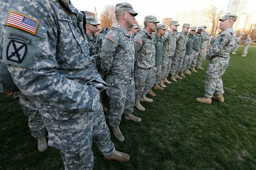 Members of the Massachusetts National Guard wait for orders on Boston Common in the evening following an explosion at the finish line of the Boston Marathon in Boston, Monday, April 15, 2013. (AP Photo/Michael Dwyer)