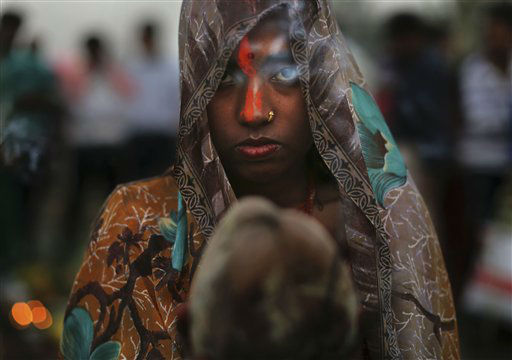 Incense smoke wafts past the face of an Indian Hindu devotee as she prays as part of rituals at sunset in the holy Yamuna River during the Chhath Puja festival in New Delhi, India, Monday, Nov. 19, 2012. Chhath prayers, an ancient Hindu festival popular amongst the working class, is performed to thank the Sun God for sustaining life on earth. &#40;AP Photo&#47;Kevin Frayer&#41; <span class=meta>(AP Photo&#47; Kevin Frayer)</span>
