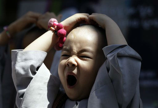 A shaven-headed young boy yawns while attending a volunteer activity in Seoul, South Korea, Thursday, May 16, 2013. He is among ten children who entered a temple to have an experience of monks&#39; life for three weeks, called Little Buddha Camp, to celebrate upcoming Buddha&#39;s birthday on May 17. &#40;AP Photo&#47;Lee Jin-man&#41; <span class=meta>(AP Photo&#47; Lee Jin-man)</span>