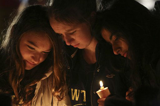 Kate Suba, left, Jaden Albrecht, center, and Simran Chand pay their respects at one of the makeshift memorials in honor of the victims of the Sandy Hook Elementary School shooting, Sunday, Dec. 16, 2012, in Newtown, Conn. A gunman opened fire at the school on Friday, killing 26 people, including 20 children before killing himself on Friday. &#40;AP Photo&#47;Mary Altaffer&#41; <span class=meta>(AP Photo&#47; Mary Altaffer)</span>