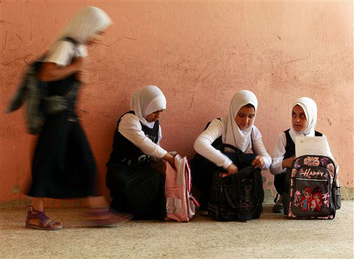 Iraqi school children walk together out of their classroom, in the Sadr City neighborhood of Baghdad, Iraq, Sunday, Sept. 23, 2012. Students nationwide returned to school on Sunday morning after three months of summer vacation. &#40;AP Photo&#47;Hadi Mizban&#41; <span class=meta>(AP Photo&#47; Hadi Mizban)</span>
