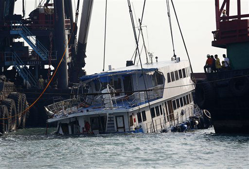 A half submerged boat is lifted by cranes Tuesday Oct. 2, 2012 after Monday night&#39;s collision near Lamma Island, off the southwestern coast of Hong Kong Island. The boat packed with revelers on a long holiday weekend collided with a ferry and sank, killing at least 36 people and injuring dozens, authorities said.  &#40;AP Photo&#47;Vincent Yu&#41; <span class=meta>(AP Photo&#47; Vincent Yu)</span>