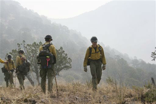 FILE - In this June 2, 2012 file photo, firefighters from the Granite Mountain Hotshots of Prescott, Ariz. cut a fire line along a mountain ridge in the Gila National Forest outside Mogollon, N.M. On Sunday, June 30, 2013, a fast-moving wildfire killed 19 firefighters from this group after the blaze raced through the central Arizona town of Yarnell, about 85 miles northwest of Phoenix. &#40;AP Photo&#47;U.S. Forest Service, Tara Ross&#41; <span class=meta>(AP Photo&#47; Tara Ross)</span>