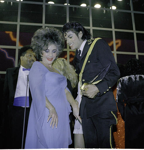 Actress Elizabeth Taylor with Michael Jackson relax after singing &#34;We are the World&#34; at the close of the American Music Awards Monday, Jan. 28, 1986 in Los Angeles. Jackson is holding the Award he shared with Quincy Jones for the song thye co-wrote &#34;We Are The World&#34;. &#40;AP Photo&#47;Nick Ut&#41; <span class=meta>(AP Photo&#47; NICK UT)</span>