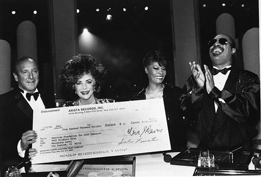 Actress Elizabeth Taylor along with Arista Records president Clive Davis, left, display a &#36;500,000 check with singers Dionne Warwick and Stevie Wonder Tuesday evening, Jan 29, 1986, in Hollywood, Calif. The check represents the proceeds from the singer&#39;s hit record &#34;That&#39;s What Friends Are For,&#34; which will go towards AIDS research.  &#40;AP Photo&#47;Nick Ut&#41; <span class=meta>(AP Photo&#47; NICK UT)</span>