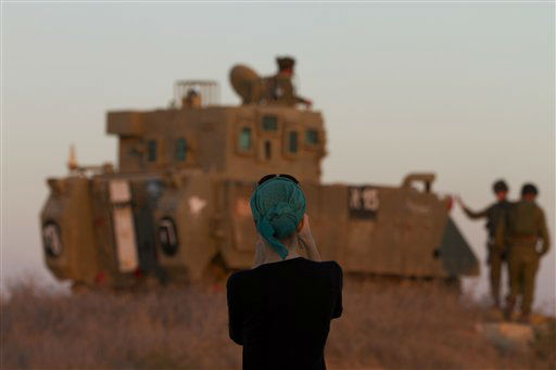 A woman photographs Israeli soldiers on top an armored personel carrier close to the Israel Gaza Border, southern Israel,Thursday, Nov. 15, 2012. Israel&#39;s prime minister says the army is prepared for a &#34;significant widening&#34; of its operation in the Gaza Strip. Benjamin Netanyahu told reporters on Thursday that Israel has &#34;made it clear&#34; it won&#39;t tolerate continued rocket fire on its civilians. &#40;AP Photo&#47;Ariel Schalit&#41; <span class=meta>(AP Photo&#47; Ariel Schalit)</span>