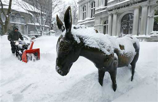 A worker clears as he passes a snow-covered donkey statue outside Old City Hall in Boston, Saturday, Feb. 9, 2013. The Boston area received about two feet of snow from a winter storm. A howling storm across the Northeast left the New York-to-Boston corridor shrouded in 1 to 3 feet of snow Saturday, stranding motorists on highways overnight and piling up drifts so high that some homeowners couldn&#39;t get their doors open. More than 650,000 homes and businesses were left without electricity. &#40;AP Photo&#47;Charles Krupa&#41; <span class=meta>(AP Photo&#47; Charles Krupa)</span>