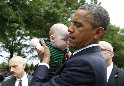 President Barack Obama picks up 4-month-old Parker Cornell of Hubert, N.C., while visiting Section 60 on Memorial Day at Arlington National Cemetery in Arlington, Va., Monday, May 27, 2013. &#40;AP Photo&#47;Molly Riley&#41; <span class=meta>(AP Photo&#47; Molly Riley)</span>