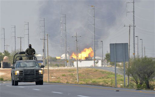 A Mexican army vehicle patrols on a road as fire and smoke rise from a gas pipeline distribution center in Reynosa, Mexico near Mexico&#39;s border with the United States, Tuesday Sept. 18, 2012. Mexico&#39;s state-owned oil company, Petroleos Mexicanos, also known as Pemex said the fire had been extinguished and the pipeline had been shut off but ten people were killed during the incident. &#40;AP Photo&#47;El Manana de Reynosa&#41; <span class=meta>(AP Photo&#47; El Manana de Reynosa)</span>