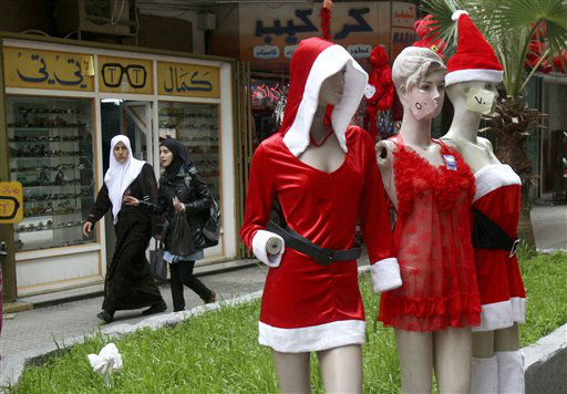 Palestinian women walk behind mannequins decorated for Valentine&#39;s Day, outside a shop in the West Bank city of Nablus, Thursday, Feb. 14, 2012. Valentine&#39;s Day is a festival of romantic love and is celebrated in many countries over the world by giving cards, flowers or gifts to spouses or partners. &#40;AP Photo&#47;Nasser Ishtayeh&#41; <span class=meta>(AP Photo&#47; Nasser Ishtayeh)</span>