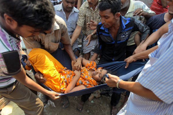 "<div class=""meta image-caption""><div class=""origin-logo origin-image ""><span></span></div><span class=""caption-text"">Rescuers carry a woman after an eight-story building housing several garment factories collapsed in Savar, near Dhaka, Bangladesh, Wednesday, April 24, 2013. Dozens were killed and many more are feared trapped in the rubble. (AP Photo/ A.M. Ahad) (AP Photo/ A.M. Ahad)</span></div>"