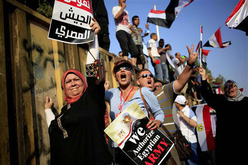 Opponents of Egypt&#39;s Islamist President Mohammed Morsi chant slogans during a protest outside the presidential palace, in Cairo, Egypt, Wednesday, July 3, 2013. The poster with partial translation of Arabic reads, &#34;we support the Egyptian military.&#34; The deadline on the military&#39;s ultimatum to President Mohammed Morsi has expired, with 48 hours passing since the time it was issued. Giant cheering crowds of Morsi&#39;s opponents have been gathered in Cairo&#39;s Tahrir Square and other locations nationwide, waving flags furiously in expection that the military will act to remove the Islamist president after the deadline ends.  &#40;AP Photo&#47;Khalil Hamra&#41; <span class=meta>(AP Photo&#47; Khalil Hamra)</span>