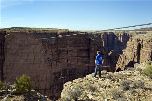 Aerialist Nik Wallenda looks across the canyon before walking a 2-inch-thick steel cable that took him a quarter mile over the Little Colorado River Gorge in northeastern Arizona on Sunday, June 23, 2013. The daredevil successfully traversed the tightrope strung 1,500 feet above the chasm near the Grand Canyon in just more than 22 minutes, pausing and crouching twice as winds whipped around him and the cable swayed. &#40;AP Photos&#47;Discovery Channel, Tiffany Brown&#41; <span class=meta>(AP Photo&#47; Tiffany Brown)</span>