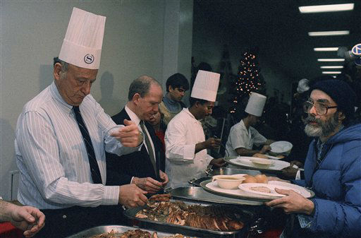 New York City Mayor Edward Koch, left, helps serve a Christmas meal to the hungry at Albert Hall on Friday, Dec. 25, 1987 in Manhattan, New York.   Koch pitched in for a few minutes of serving during his Christmas visit to the center. &#40;AP Photo&#47;Marty Lederhandler&#41; <span class=meta>(AP Photo&#47; Marty Lederhandler)</span>