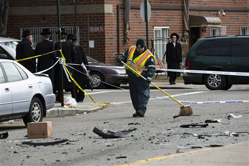 A worker clears debris  from a fatal accident that claimed the lives of two expectant parents, Sunday, March 3, 2013, in the Brooklyn borough of New York. A driver struck the car the couple were riding in early Sunday morning, killing both parents while their baby, who?was born prematurely, survived?and is?in critical condition. &#40;AP Photo&#47;John Minchillo&#41; <span class=meta>(AP Photo&#47; John Minchillo)</span>