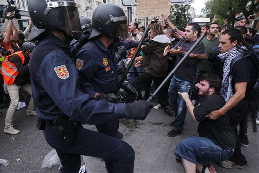 Police clash with protestors during the march to the parliament against austerity measures announced by the Spanish government in Madrid, Spain, Tuesday, Sept. 25, 2012. Spain&#39;s Parliament has taken on the appearance of a heavily guarded fortress with dozens of police blocking access from every possible angle, hours ahead of a protest against the conservative government&#39;s handling of the economic crisis. The demonstration, organized behind the slogan &#39;Occupy Congress,&#39; is expected to draw thousands of people. It is due to start around 1730 GMT Tuesday. Madrid authorities said some 1,300 police would be deployed. The protestors call for Parliament to be dissolved and fresh elections held, claiming the government&#39;s austerity measures show the ruling Popular Party misled voters to get elected last November. &#40;AP Photo&#47;Andres Kudacki&#41; <span class=meta>(AP Photo&#47; Andres Kudacki)</span>