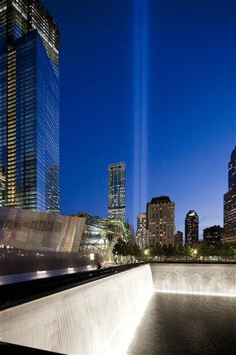 The Tribute in Light shines above a reflecting pool at the National September 11 Memorial, Tuesday, Sept. 11, 2012 in New York. On the left is 4 World Trade Center. Today marks the 11th anniversary of the terrorist attacks of Sept. 11, 2001. &#40;AP Photo&#47;Mark Lennihan&#41; <span class=meta>(AP Photo&#47; Mark Lennihan)</span>