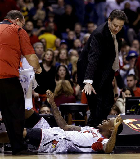 Louisville head coach Rick Pitino and trainers tend to injured guard Kevin Ware during the first half of the Midwest Regional final in the NCAA college basketball tournament against Duke, Sunday, March 31, 2013, in Indianapolis. Ware badly injured his lower right leg and had to be taken off the court on a stretcher. &#40;AP Photo&#47;Darron Cummings&#41; <span class=meta>(AP Photo&#47; Darron Cummings)</span>