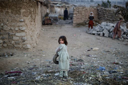 An Afghan refugee girl, looks back after picking up a tire from the ground, in a slum on the outskirts of Islamabad, Pakistan, Monday, Nov. 26, 2012. &#40;AP Photo&#47;Muhammed Muheisen&#41; <span class=meta>(AP Photo&#47; Muhammed Muheisen)</span>