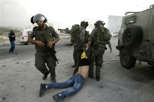 A Palestinian is arrested by Israeli security forces during a protest against the Israeli military operations in Gaza Strip near the West Bank city of Nablus, Sunday, Nov. 18, 2012. &#40;AP Photo&#47;Nasser Ishtayeh&#41; <span class=meta>(AP Photo&#47; Nasser Ishtayeh)</span>