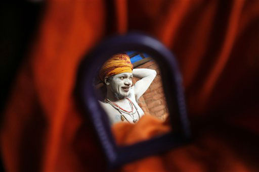 A Naga sadhu, or naked Hindu holy man, reflected on a mirror, ties his turban after taking a holy dip in the River Ganges during preparations for the upcoming over-a-month-long Mahakumbh fair in Allahabad, India, Monday, Dec. 3, 2012. Millions of Hindu pilgrims are expected to take part in the largest religious congregation on the banks of Sangam, the confluence of rivers Ganges, Yamuna and mythical Saraswati, during the festival in January 2013, which falls every twelfth year. &#40;AP Photo&#47;Rajesh Kumar Singh&#41; <span class=meta>(AP Photo&#47; Rajesh Kumar Singh)</span>