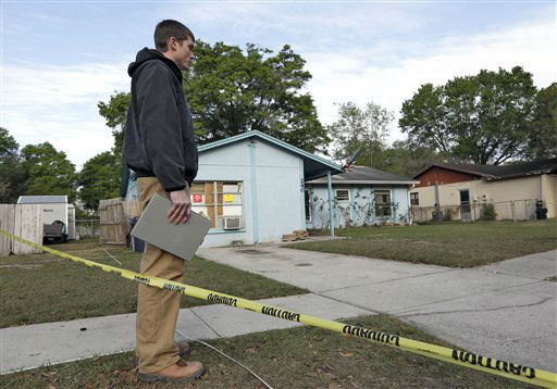An engineer stands in front of a home where sinkhole opened up on Friday, March 1, 2013, in Seffner, Fla.  A man screamed for help and disappeared as a large sinkhole opened under the bedroom of the house, his brother said Friday. The brother told rescue crews he heard a loud crash near midnight Thursday, then heard his brother screaming. The brother called police and frantically tried to help. An arriving deputy pulled him from the still-collapsing house. There&#39;s been no contact with the man since then, and neighbors on both sides of the home have been evacuated. &#40;AP Photo&#47;Chris O&#39;Meara&#41; <span class=meta>(AP Photo&#47; Chris O&#39;Meara)</span>