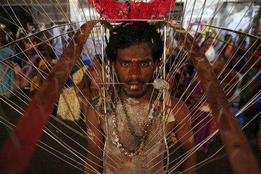 A Hindu devotee, body pierced with skewers, participates in a religious procession during Panguni Uthiram festival in Chennai, India, Tuesday, March 26, 2013. The festival is observed in the Tamil month of Panguni and is celebrated in honor of the Hindu God Murugan where devotees make offerings to lord Murugan with sacrificial feats they believe will keep them away from evil spirits. &#40;AP Photo&#47;Arun Sankar K.&#41; <span class=meta>(AP Photo&#47; Arun Sankar K)</span>
